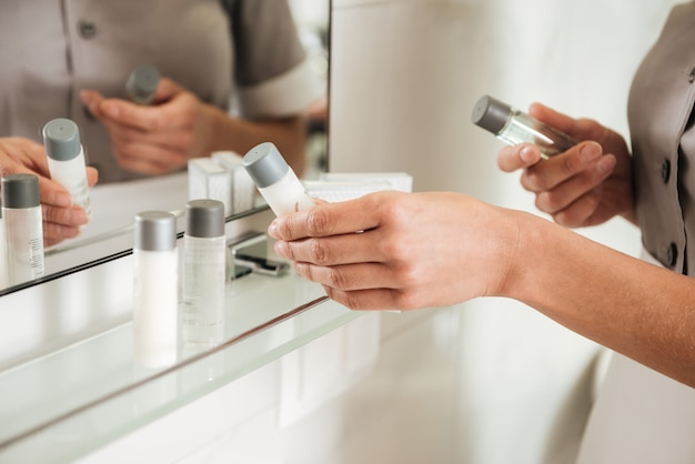 Empregada de hotel jovem colocando acessórios de banho em uma casa de banho Foto gratuita