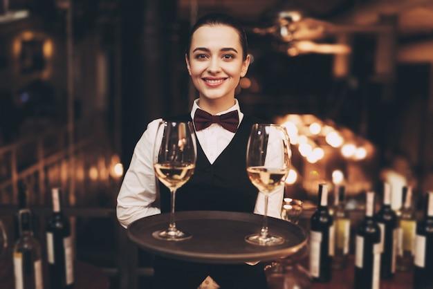 Empregada de mesa alegre que guarda a bandeja com vidros do vinho branco. Foto Premium