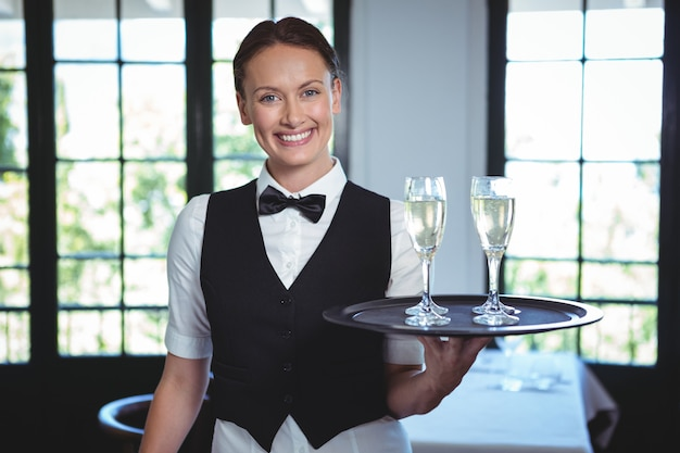 Empregada de mesa com uma bandeja de flauta de champanhe Foto Premium