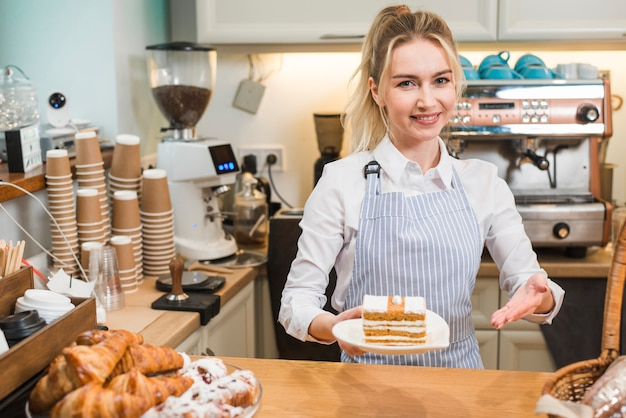 Empregada de mesa fêmea de sorriso que oferece a pastelaria na cafetaria Foto gratuita