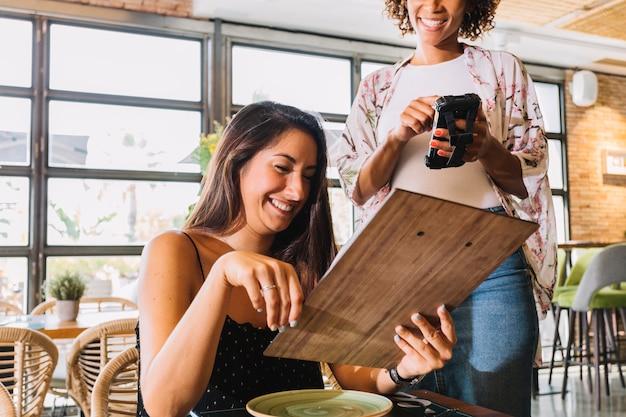 Empregada de mesa fêmea que toma o pedido no smartphone no restaurante Foto gratuita