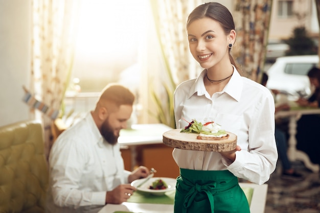 Empregada de mesa jovem retrato segurando o sanduíche no prato Foto Premium