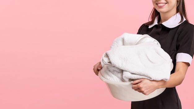 Empregada de sorriso do close-up segurando uma cesta de lavanderia Foto gratuita