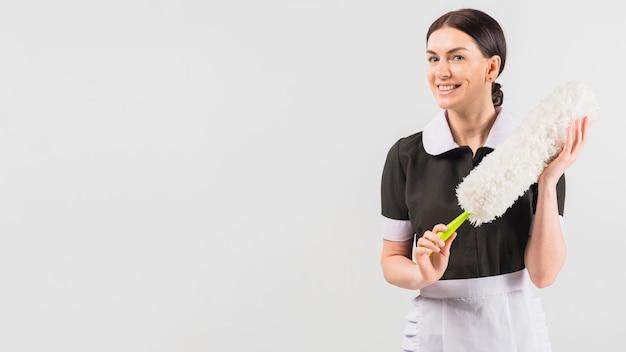 Empregada de uniforme, sorrindo com espanador Foto gratuita