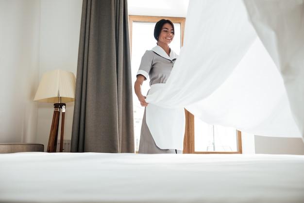 Empregada do hotel mudando lençol Foto gratuita