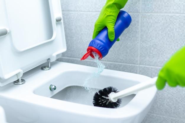 Empregada doméstica em luvas de borracha, lavar e desinfetar o banheiro usando produtos de limpeza e escova. tarefas domésticas e serviço de limpeza Foto Premium