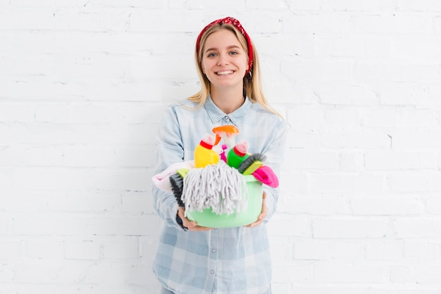 Empregada sorridente com produtos de limpeza Foto gratuita
