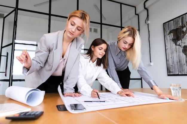 Empregadas do sexo feminino de baixo ângulo esboçar estratégia Foto gratuita