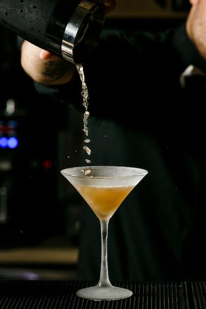 Empregado de bar considerável novo no cocktail de mistura interior do álcool da barra. p Foto Premium