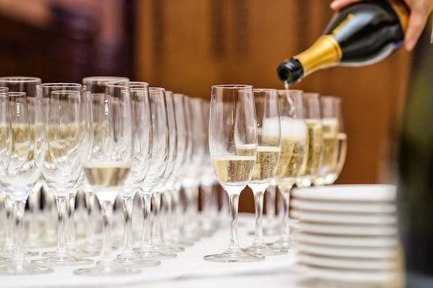 Empregado de mesa que derrama o champanhe no vidro de vinho no restaurante. Foto Premium