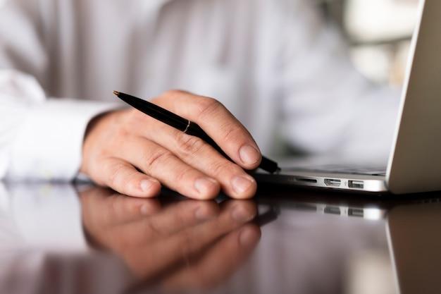Empregado irreconhecível, segurando a caneta close-up Foto gratuita