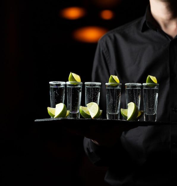 Empregado segurando uma bandeja de serviço com cocktails de limão. Foto gratuita