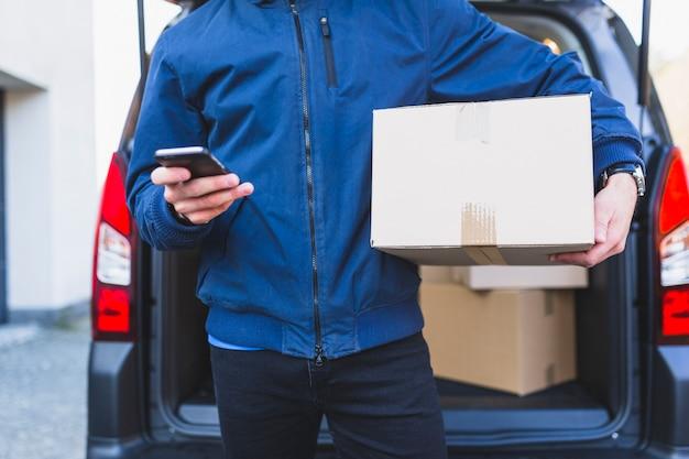 Empregador com caixa usando o telefone Foto gratuita