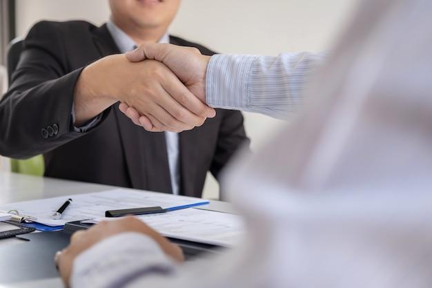 Empregador de terno e novo empregado apertando as mãos após negociação e colocação de entrevista Foto Premium