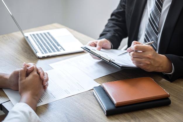 Empregador ou comitê segurando a leitura de um currículo falando durante o seu perfil de candidato, empregador de terno está conduzindo uma entrevista de emprego, emprego de gerente de recursos e conceito de recrutamento Foto Premium