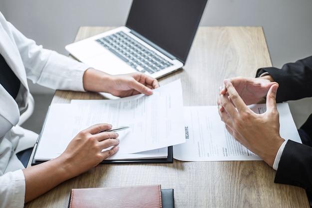 Empregador ou recrutador segurando a leitura de um currículo com a falar durante o seu perfil de candidato, o empregador de terno está conduzindo uma entrevista de emprego, emprego de gerente de recursos e conceito de recrutamento Foto Premium