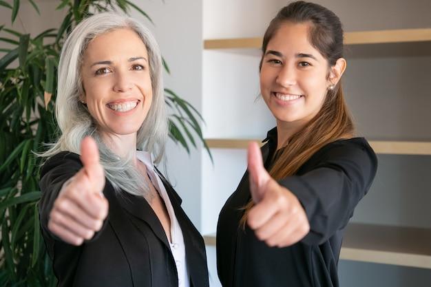 Empregadores de escritório confiantes manuseando e sorrindo. duas mulheres de negócios profissionais felizes juntos e posando na sala de reuniões. conceito de trabalho em equipe, negócios e cooperação Foto gratuita