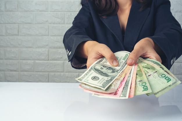 Empregados de mulher contando dinheiro em uma mesa branca Foto gratuita