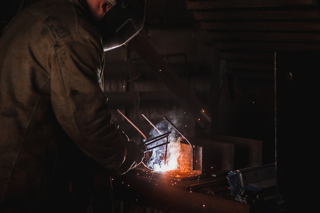 Emprego de um soldador. uma grande fábrica de produtos de concreto e soldagem sobre ela. Foto Premium
