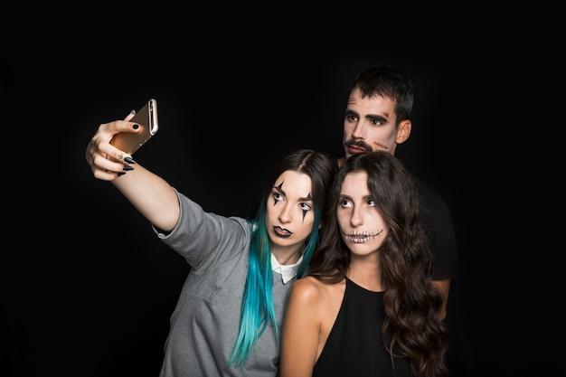 Empresa jovem com maquiagem assustador tomando selfie Foto gratuita