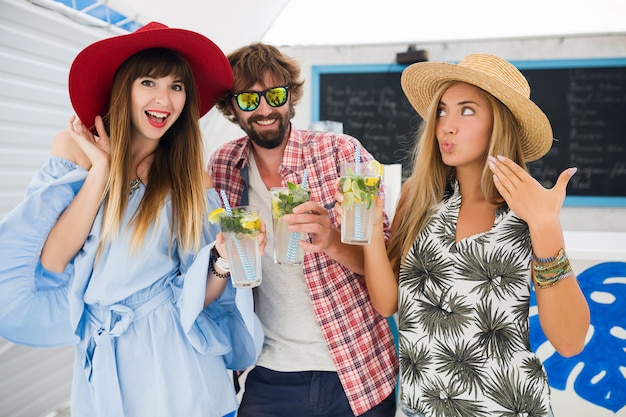 Empresa jovem hippie de amigos de férias no café de verão, bebendo coquetéis de mojito, estilo positivo feliz, sorrindo feliz, duas mulheres e um homem se divertindo juntos, conversando, flertando, romance, três Foto gratuita