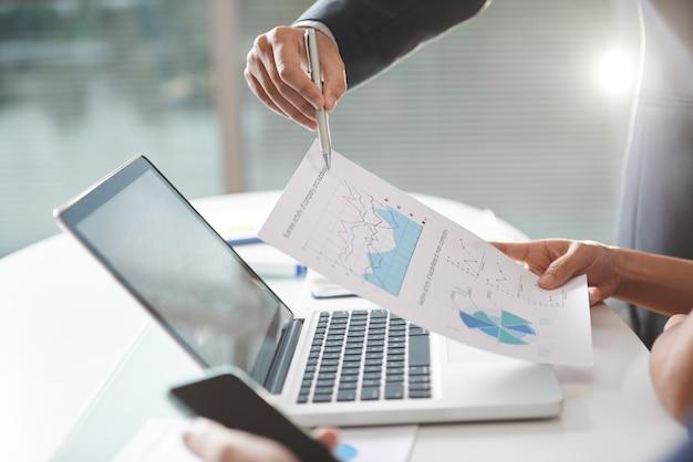Empresa moderna teem coworking usando gráficos e laptop no escritório Foto gratuita