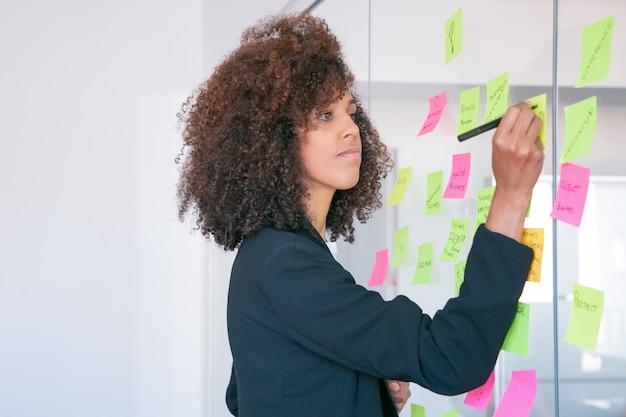 Empresária afro-americana, escrevendo na etiqueta com marcador. gerente feminina confiante e confiante, focada, compartilhando ideias para o projeto e fazendo anotações Foto gratuita