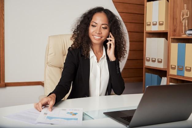 Empresária alegre tendo telefonema no escritório Foto gratuita