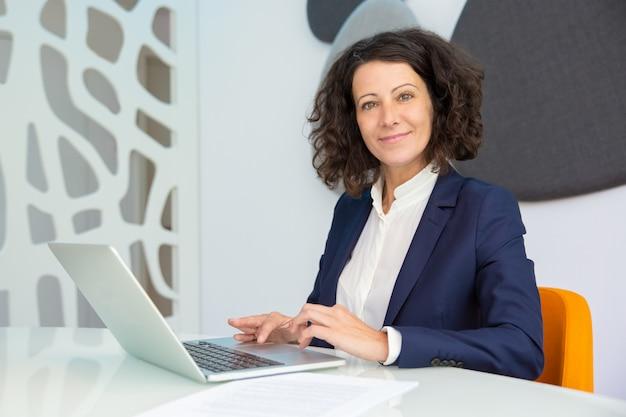 Empresária alegre usando laptop Foto gratuita
