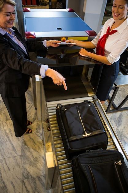 Empresária, apontando para a bagagem mantida na correia transportadora Foto gratuita