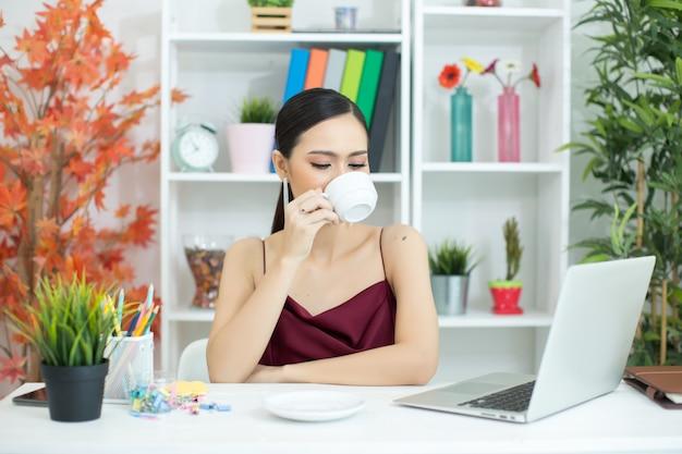Empresária asiática fazer uma pausa para o café depois de trabalhar no computador portátil na mesa Foto gratuita