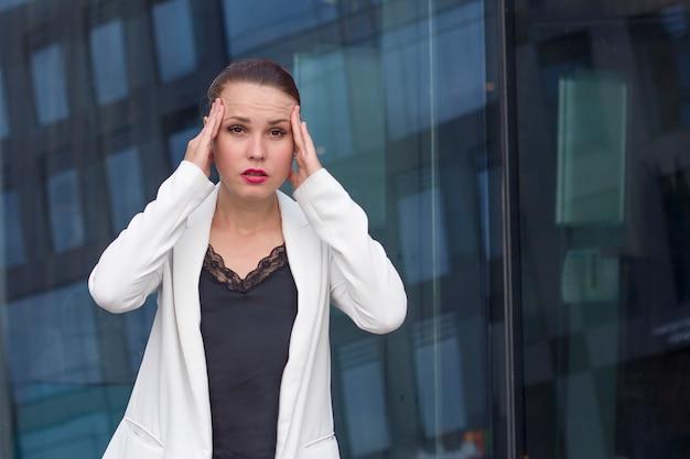 Empresária cansada exausta surpresa, sofrendo de dor de cabeça ou enxaqueca, segurando a cabeça com as mãos, olhando para a câmera ao ar livre. doente no trabalho, trabalho estressante. foi demitido. sobrecarregado fêmea no casaco. Foto Premium