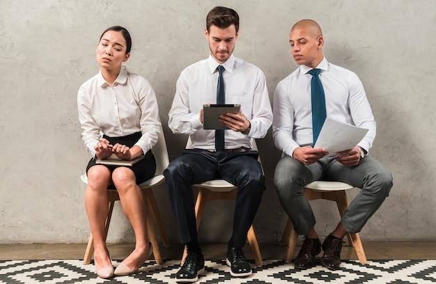 Empresária corporativa curiosa interessados olhando para tablet digital de colegas Foto gratuita