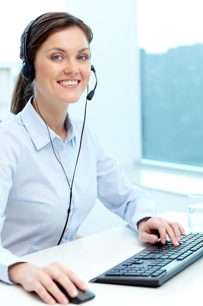 Empresária de trabalho on-line com um laptop e fone de ouvido Foto gratuita