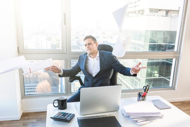 Empresária despreocupada jogando documentos no escritório Foto gratuita