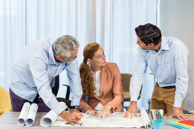 Empresária e colegas de trabalho discutindo blueprint Foto Premium