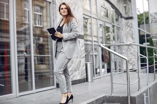 Empresária elegante, trabalhando em uma cidade e usar o notebook Foto gratuita