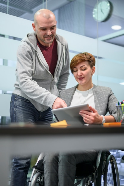 Empresária em cadeira de rodas, conversando com um colega de trabalho Foto gratuita