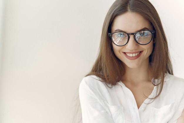 Empresária em uma camisa branca, sentado no escritório Foto gratuita