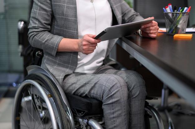Empresária em vista média de cadeira de rodas Foto gratuita