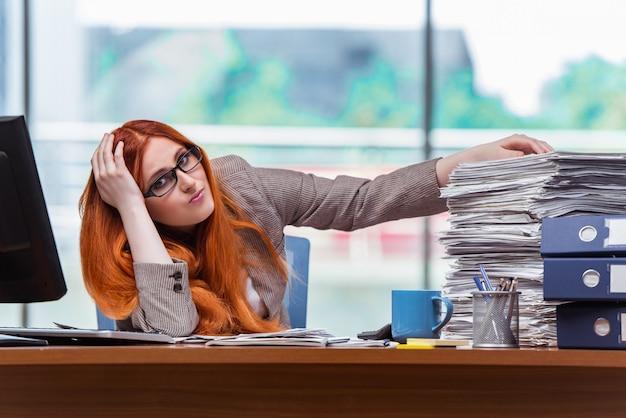 Empresária estressada com pilha de papéis Foto Premium