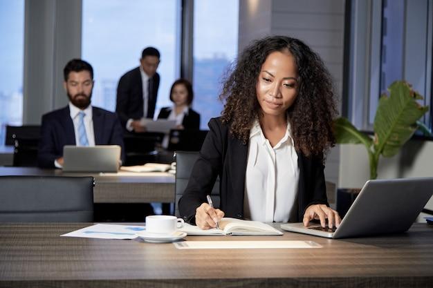 Empresária étnica trabalhando no escritório moderno Foto gratuita