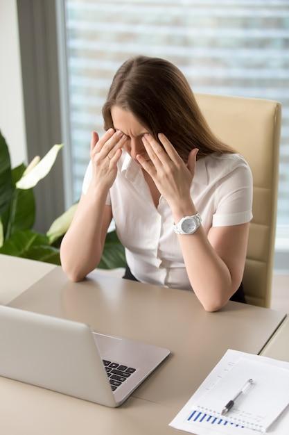 Empresária exausta, sentado na mesa no escritório Foto gratuita