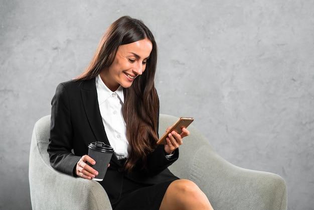 Empresária feliz segurando o copo de café descartável olhando para celular Foto gratuita