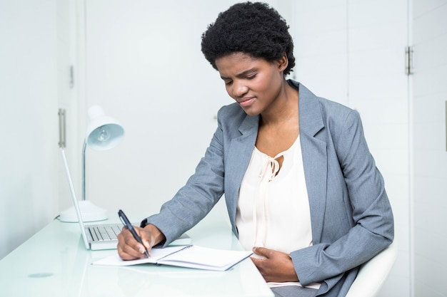 Empresária grávida escrevendo no notebook no escritório Foto Premium