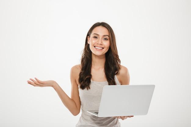 Empresária incrível segurando laptop prata e gesticulando com sorriso, sobre parede branca Foto gratuita
