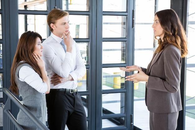 Empresária, interagindo com a equipe no escritório Foto Premium