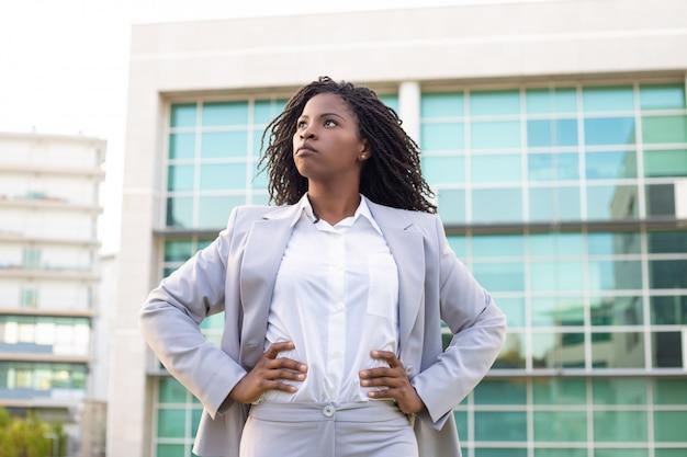 Empresária jovem confiante com as mãos na cintura Foto gratuita