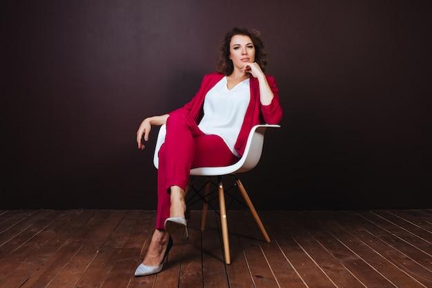 Empresária jovem sorridente, sentado na cadeira do escritório, sobre fundo escuro Foto gratuita