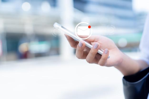 Empresária mão segure o dispositivo de smartphone para abrir emails não lidos Foto Premium